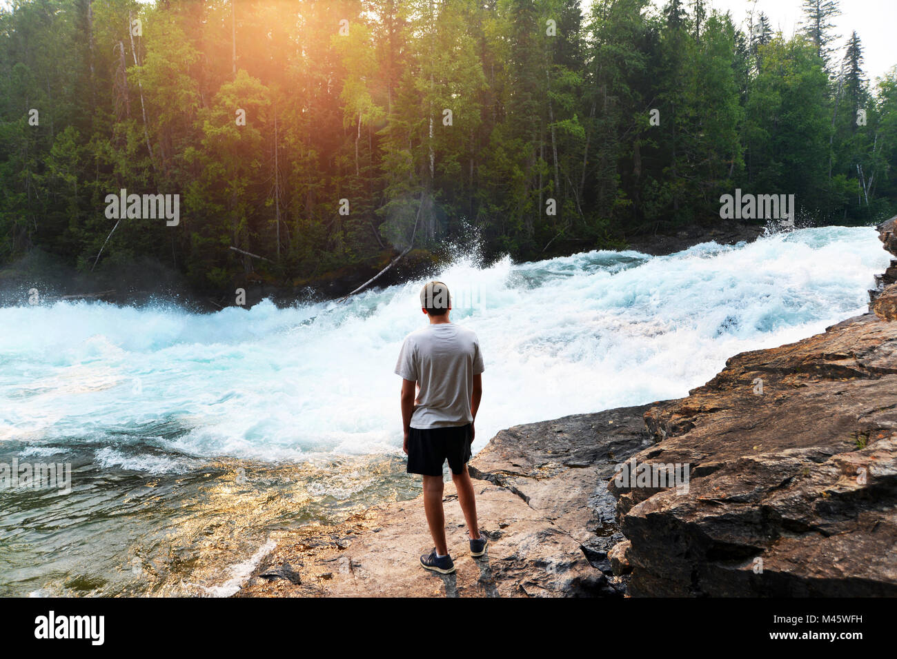 Teenage boy watches salmon leaping at Grey Wells National Park, Clearwater, British Columbia, Canada. - Stock Image