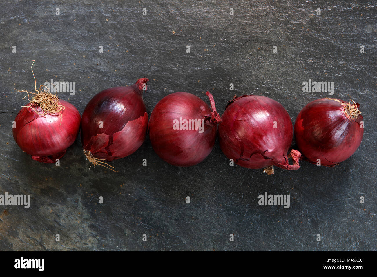 Red onions in a line on dark slate table top - Stock Image