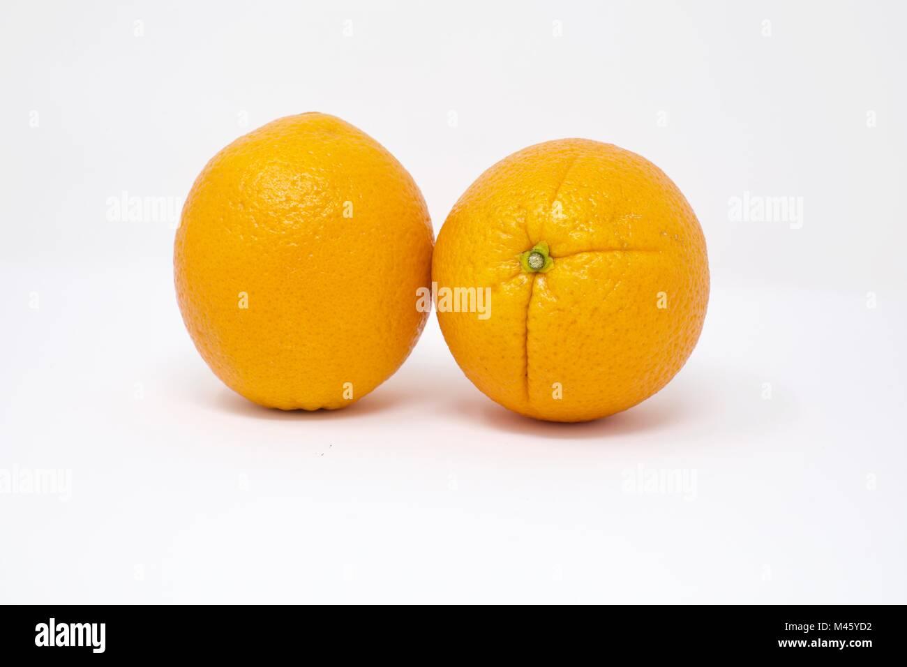 Two fresh whole Oranges (Citrus sinensis) on a white background - Stock Image