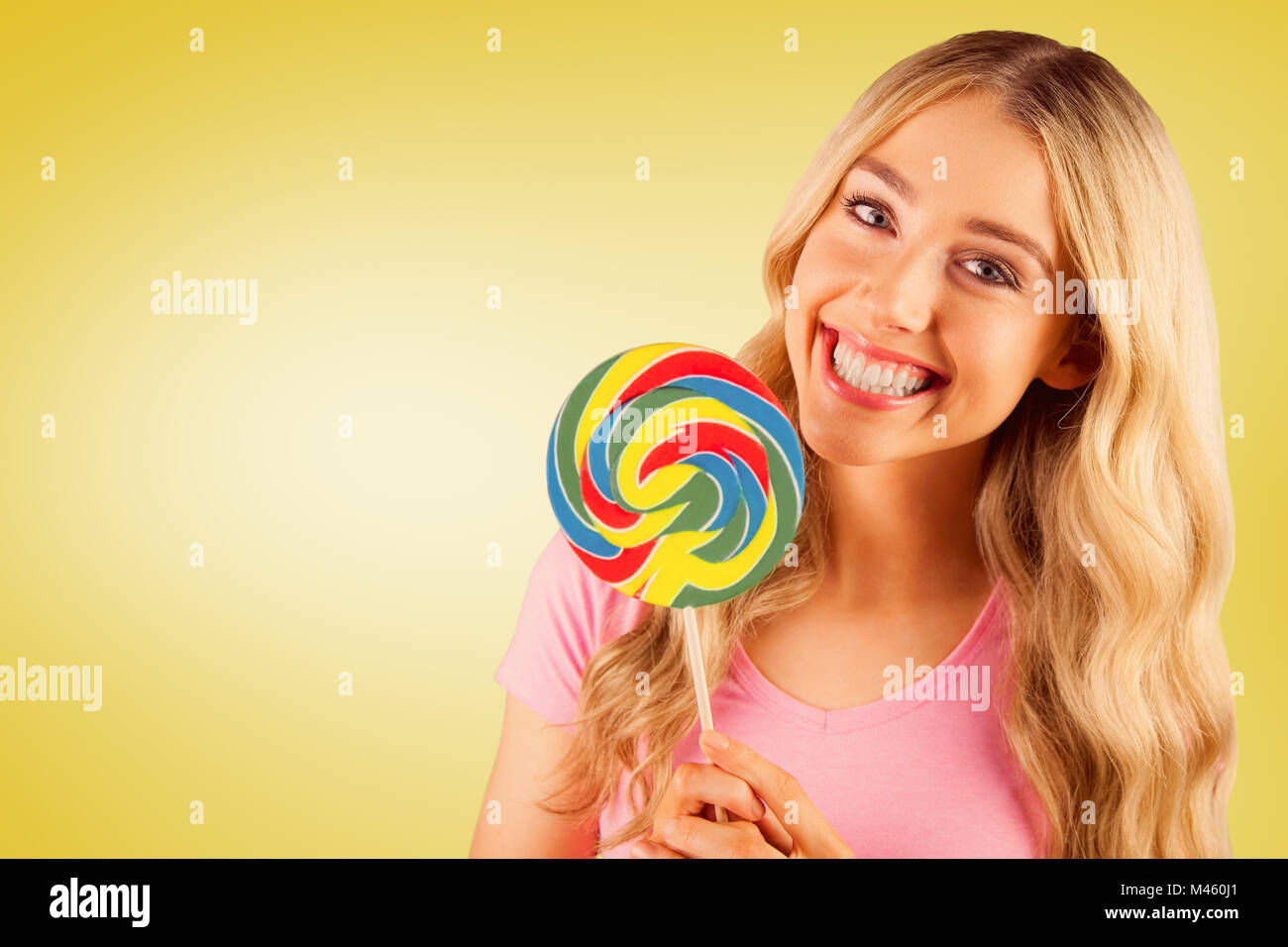 Composite image of a beautiful woman holding a giant lollipop - Stock Image