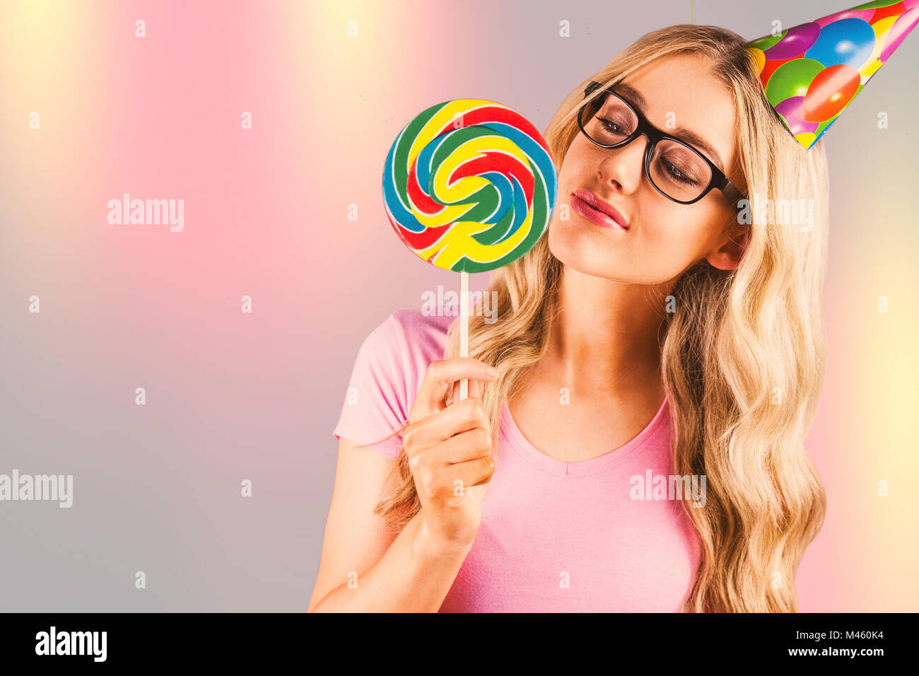 Composite image of a beautiful hipster holding a giant lollipop - Stock Image