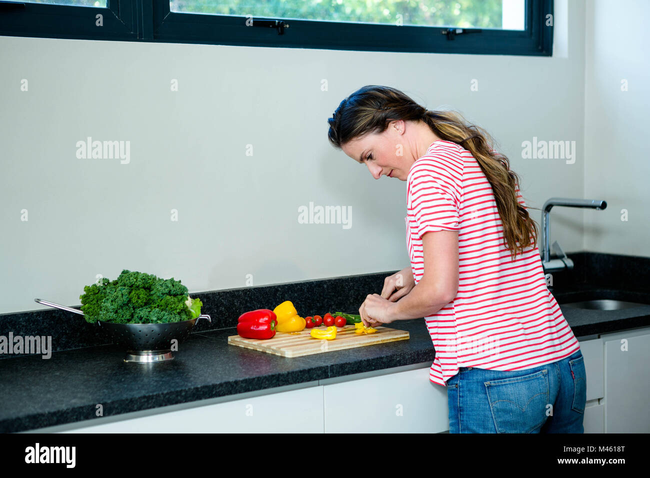 thoughtfull woman preparing vegetables for dinner - Stock Image