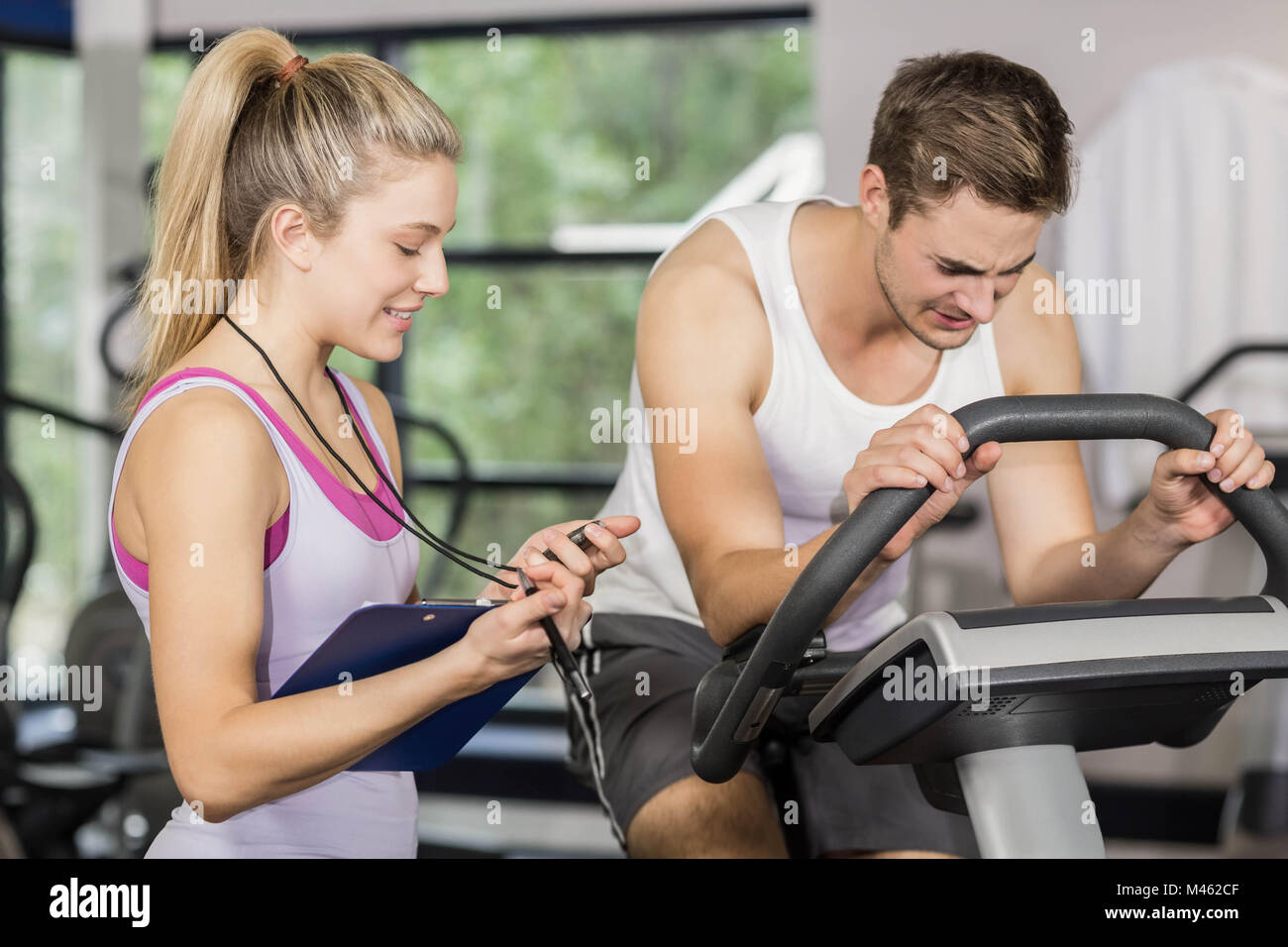Trainer woman talking with a man doing exercise bike Stock Photo