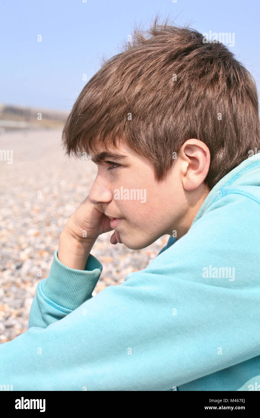 Fair-haired  teenage boy in a blue sweat  alone on a beach looking sad and unhappy in autumn sunshine - Stock Image