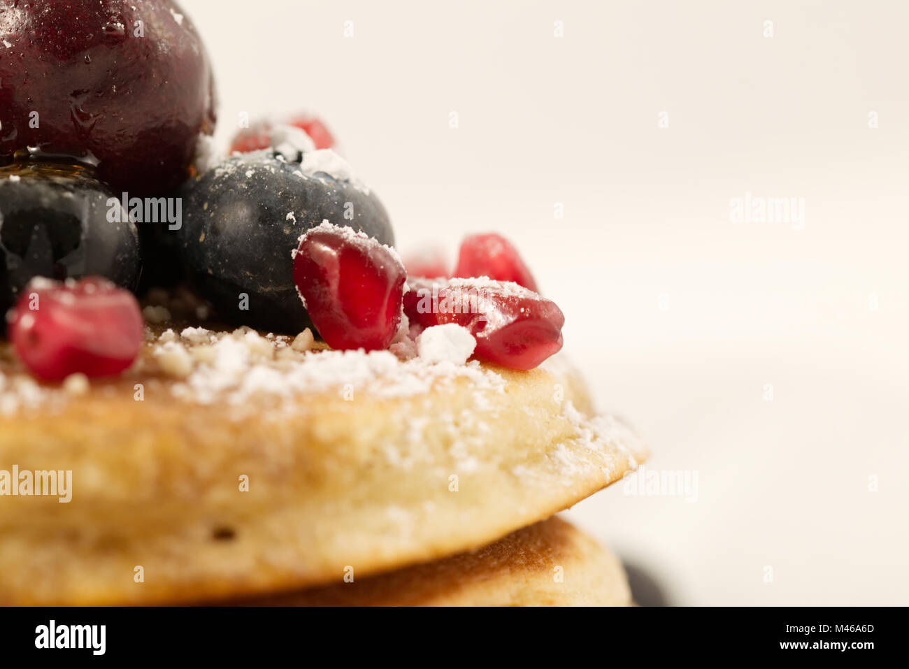 Breakfast pancakes topped with blueberries, cherries, pomegranate seeds and icing sugar (powdered sugar) and maple - Stock Image
