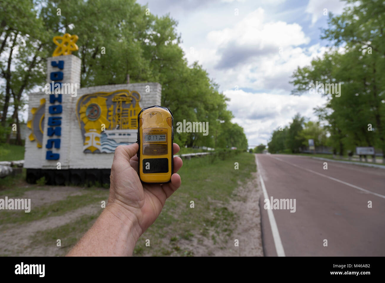 A man takes a radiation reading with a Geiger counter at the entrance to Chernobyl - Stock Image