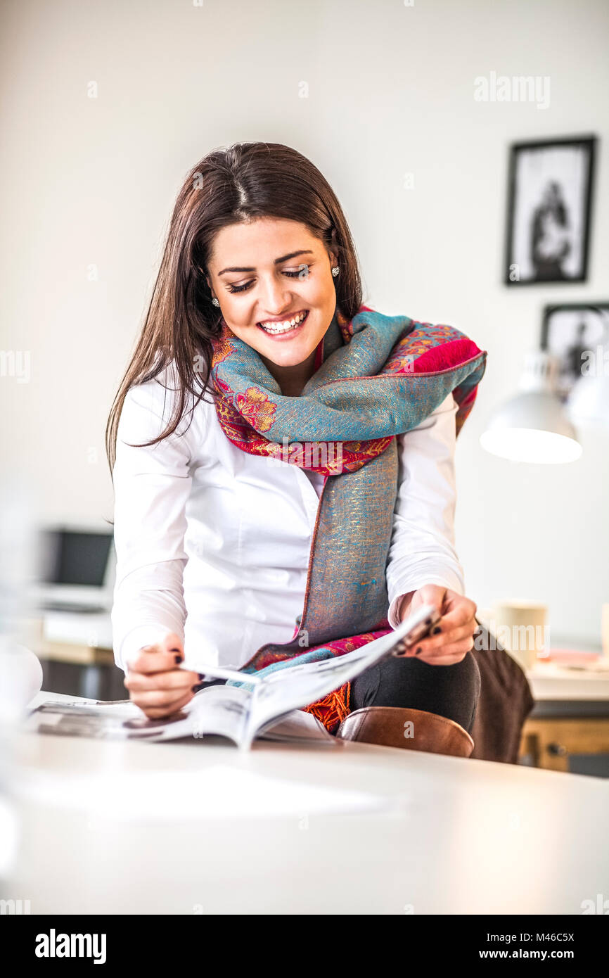 Smiling young businesswoman analyzing brochure in creative office - Stock Image