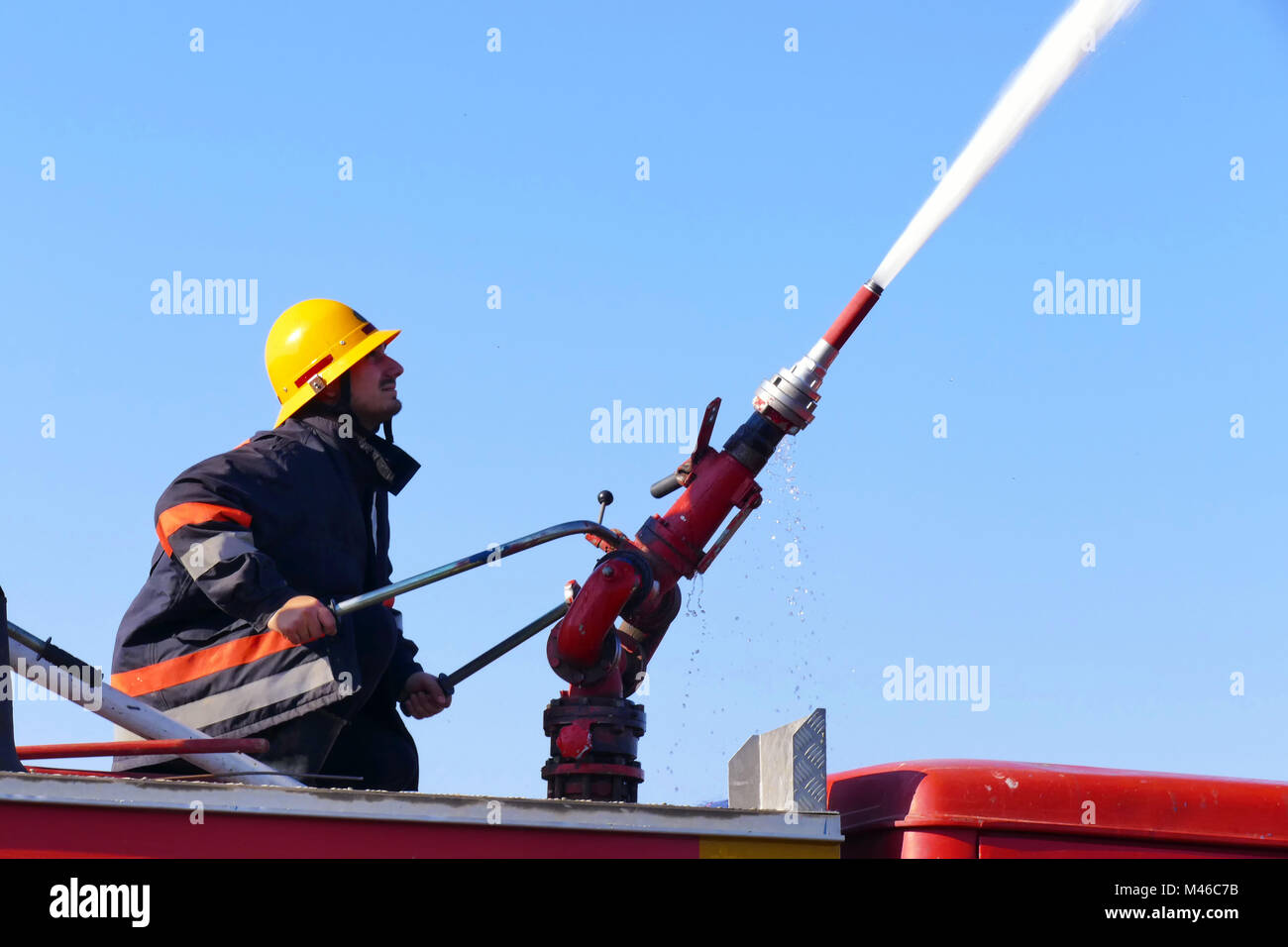 Firefighter with a water cannon - Stock Image