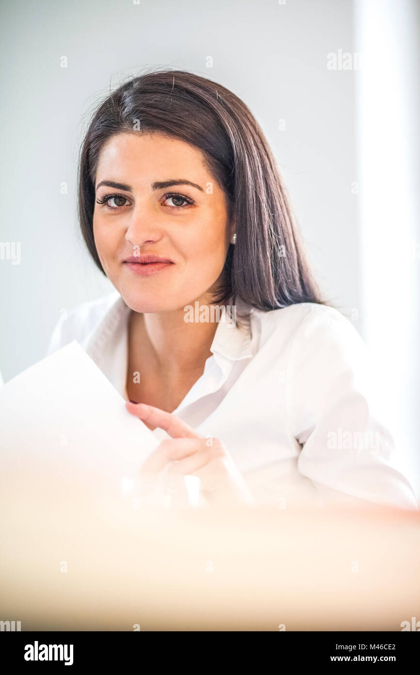 Portrait of young businesswoman reviewing documents in office - Stock Image