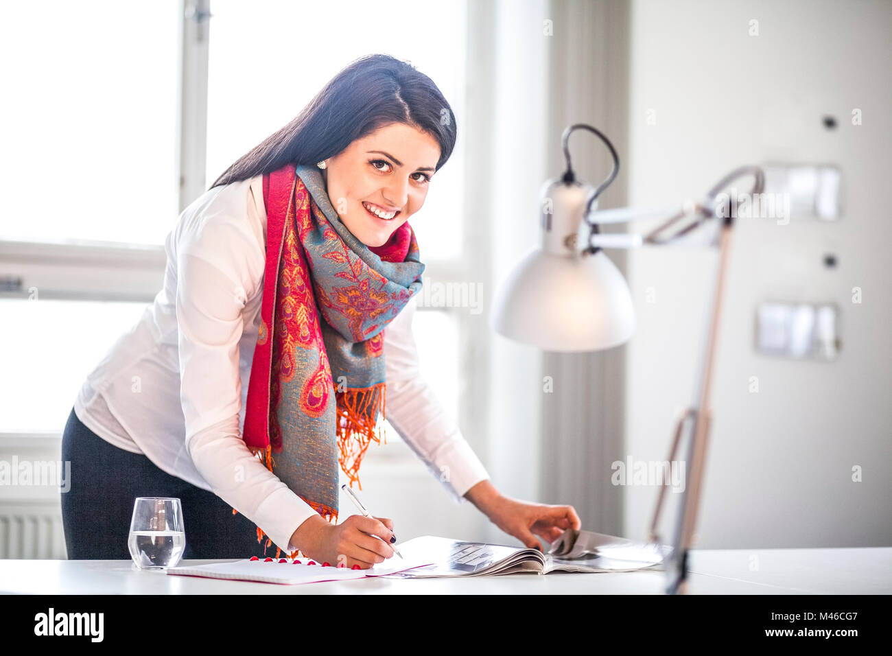 Portrait of businesswoman writing notes at desk in office - Stock Image