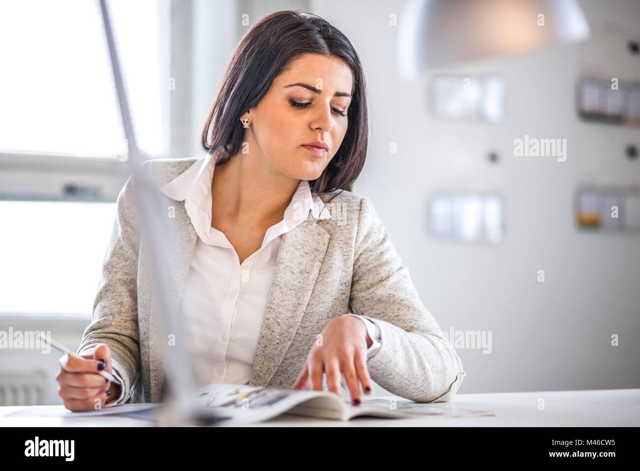 Businesswoman reading brochure while taking notes in office - Stock Image