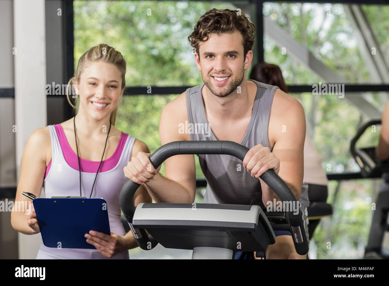 Trainer woman with a man doing exercise bike - Stock Image