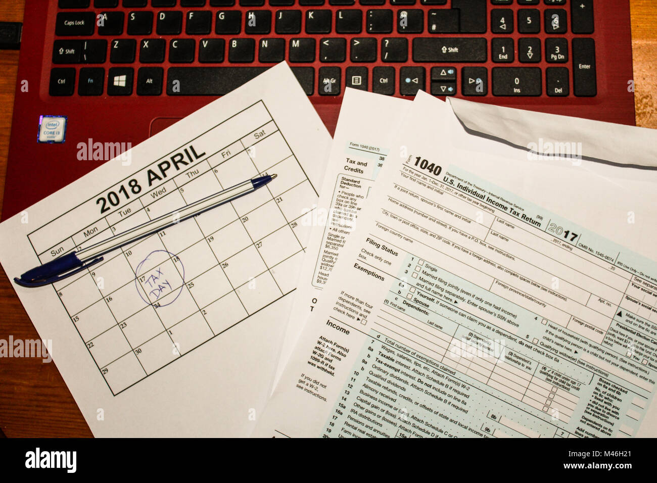 Calendar and form 1040 income tax form for 2017 showing tax day for filing is April 17 2018 - Stock Image