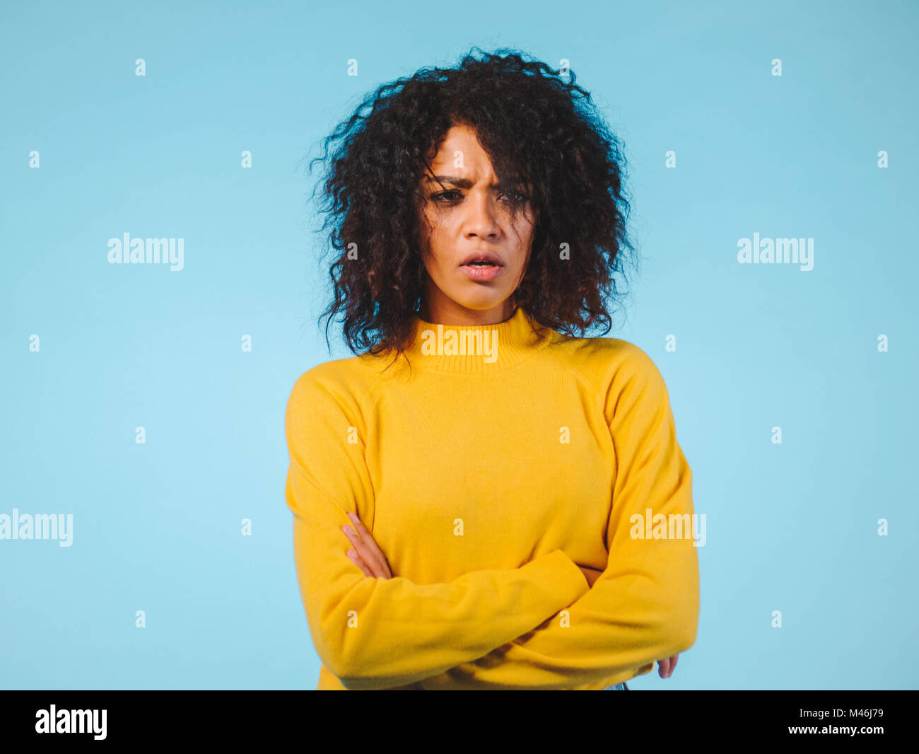 Angry annoyed young housewife keeping arms crossed and staring at camera with sceptical and distrustful look, feeling - Stock Image