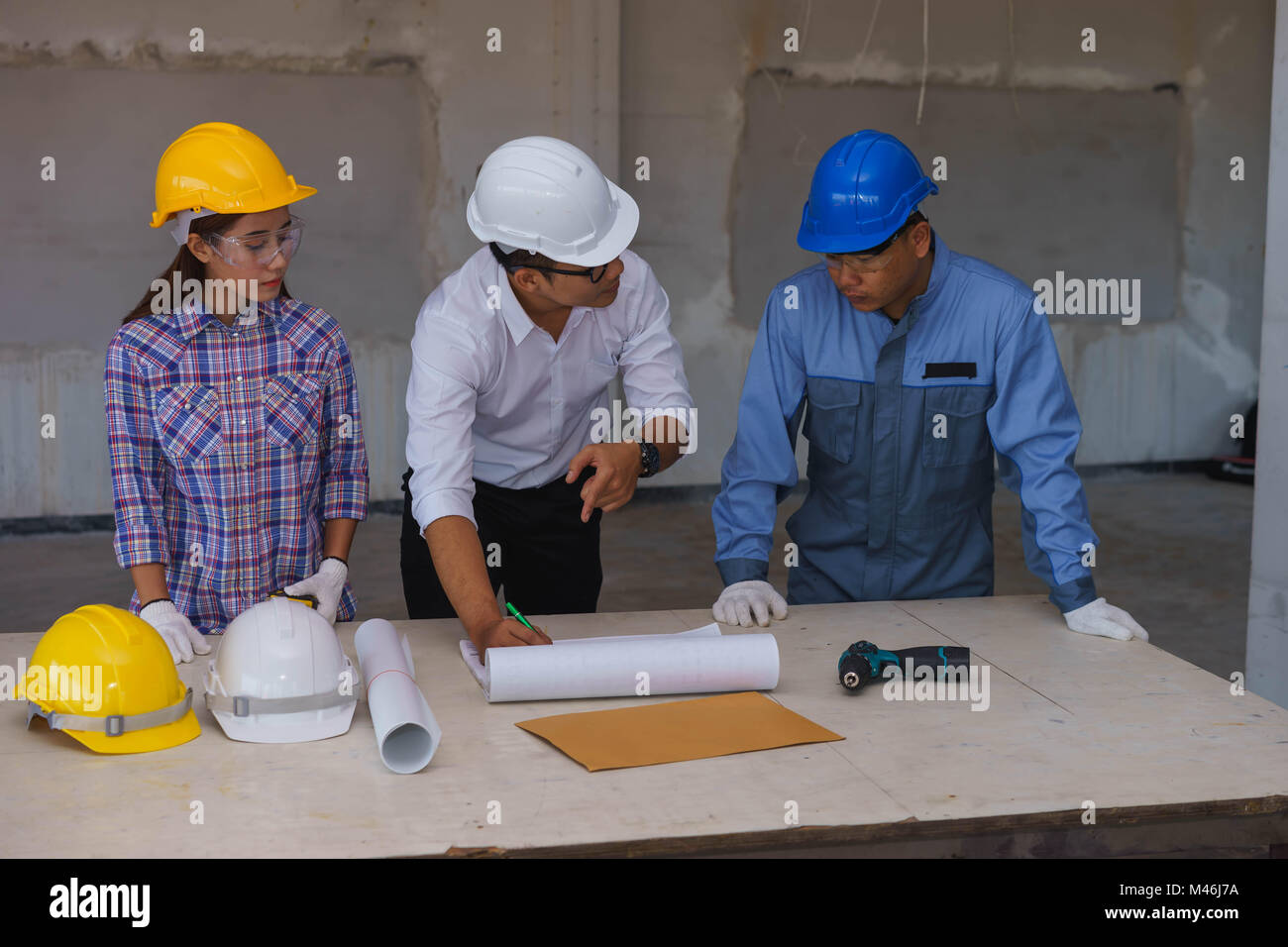 engineer is explaining work to technician and female worker at a construction site in bangkok thailand