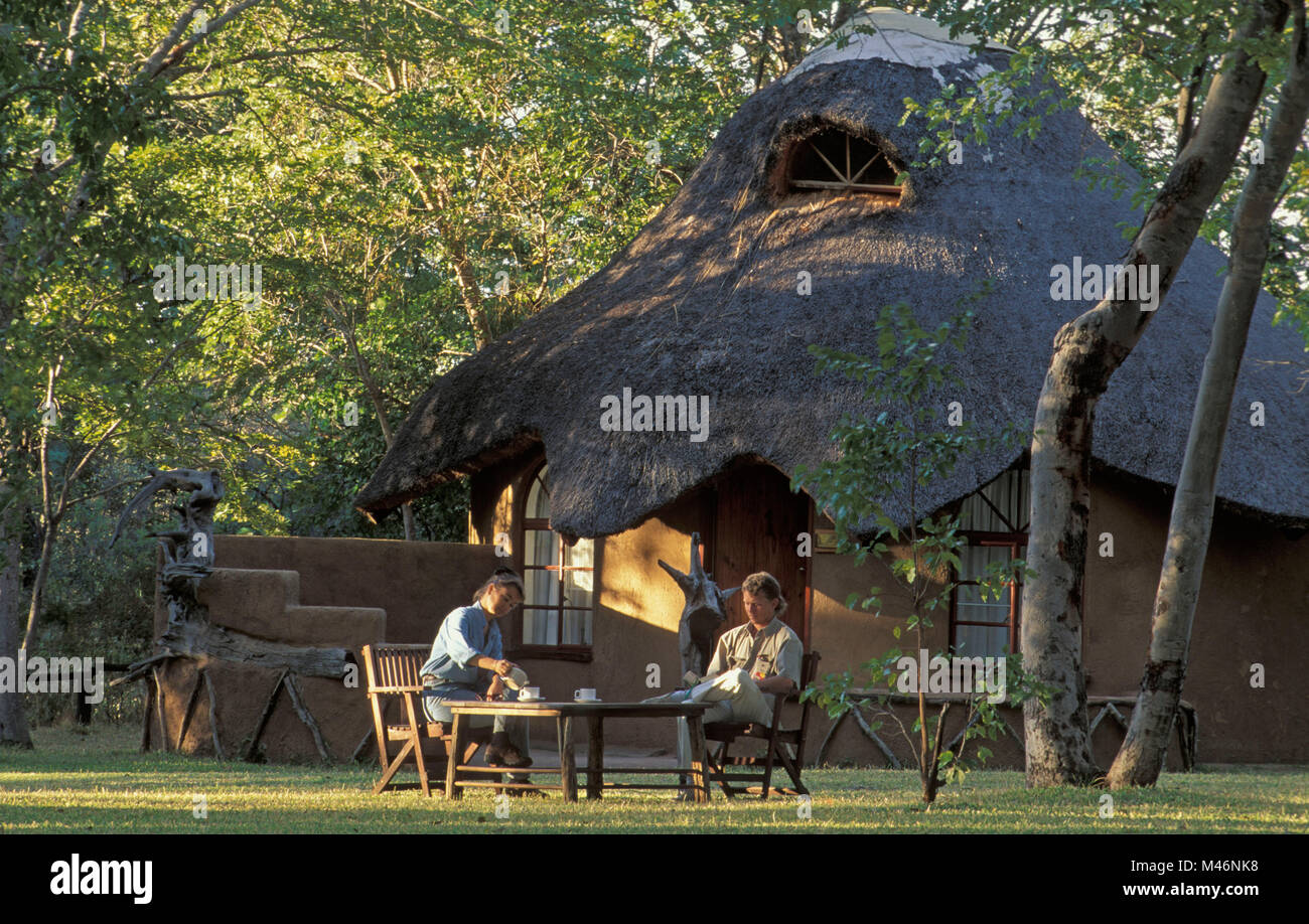 Zimbabwe. Hwange National Park. Tourists. Sable Valley Lodge. Man and woman having tea. Stock Photo