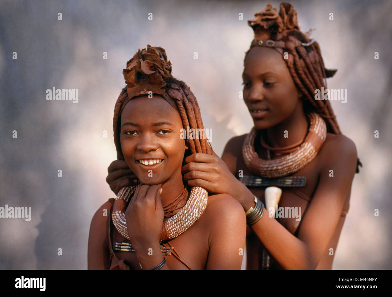 Namibia. Kaokoveld, near Opuwo. Himba tribe. Women arranging their hair. - Stock Image