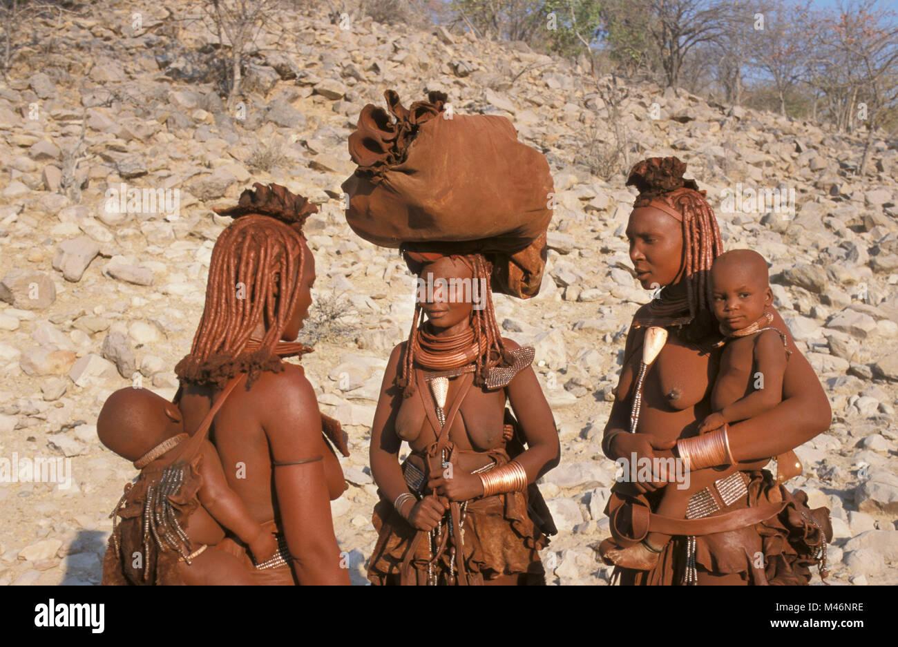 Namibia. Kaokoveld, near Opuwo. Himba tribe. Women, mothers and baby. - Stock Image