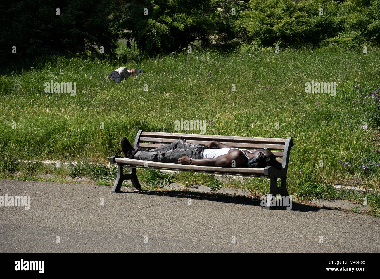 Rome, Italy: A black boy sleeps on a bench in the sun - Stock Image