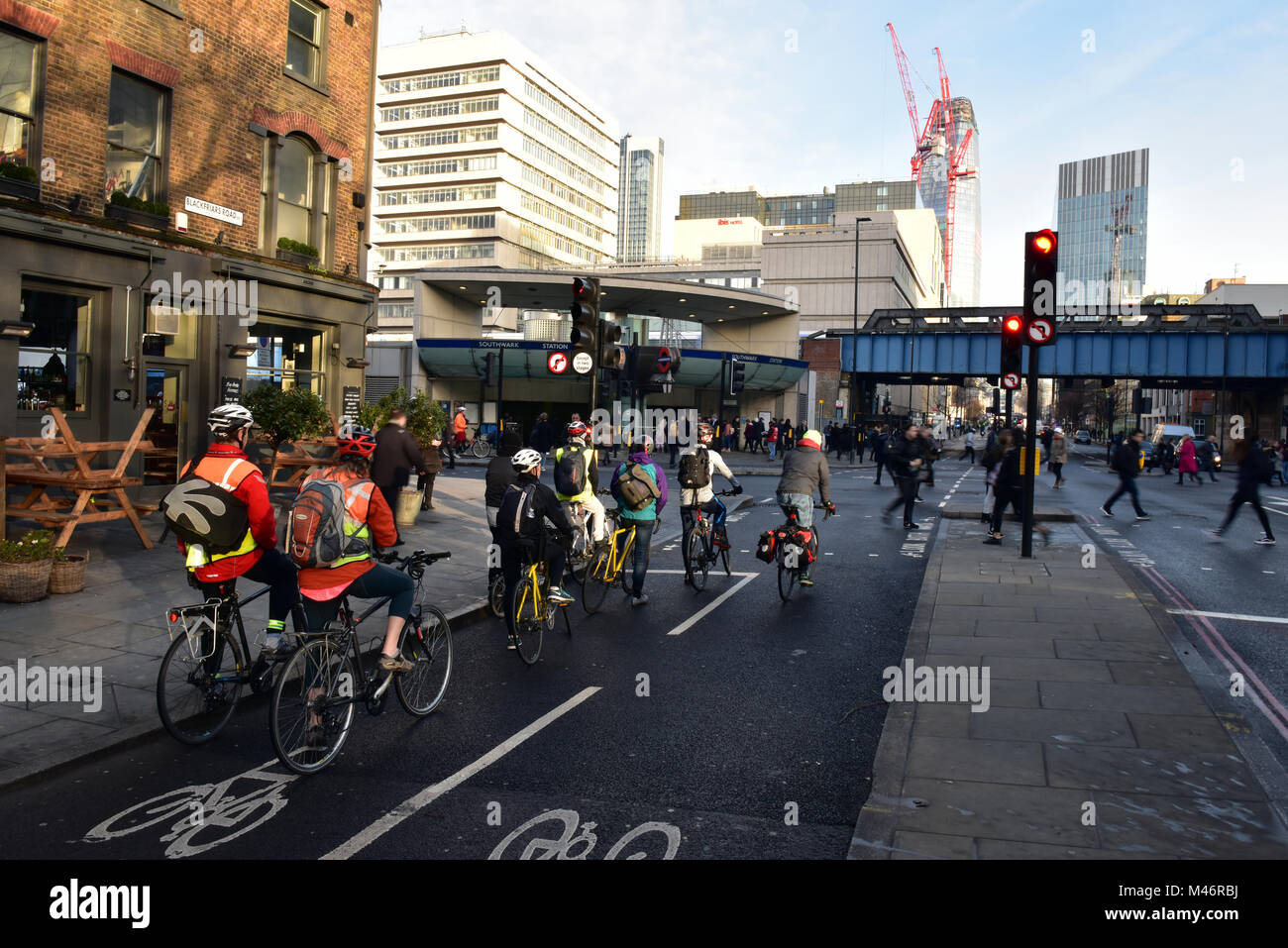 cyclists waiting at a red light at a road junction opposite to southwark tube station during the morning rush hour Stock Photo