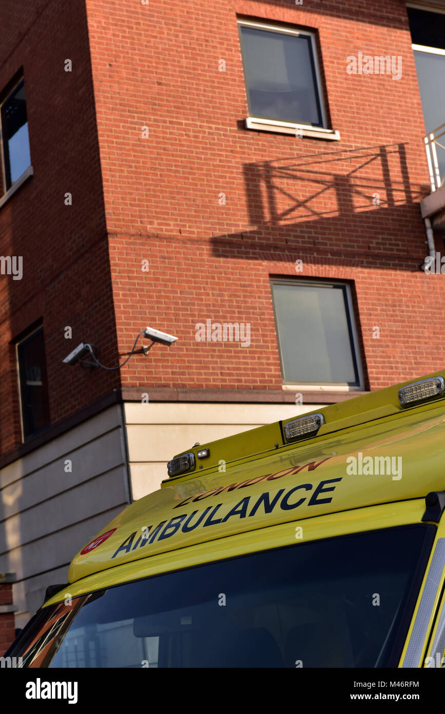 A london ambulance service NHS ambulance parked outside of a red brick building attending an emergency in the capital - Stock Image