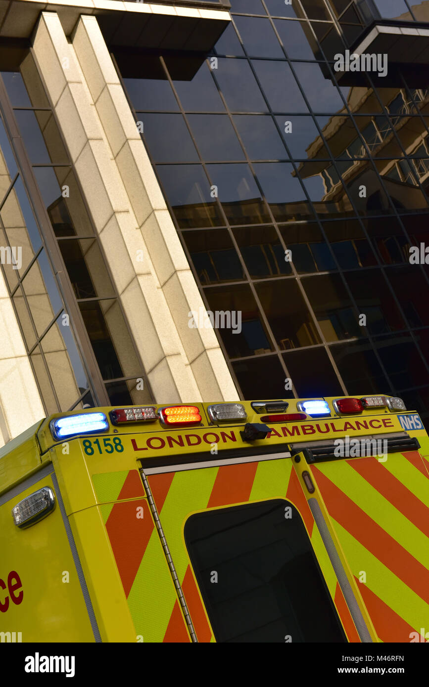 an emergency amulance in the centre of london with lights flashing attending a 999 call in a busy office commercial - Stock Image