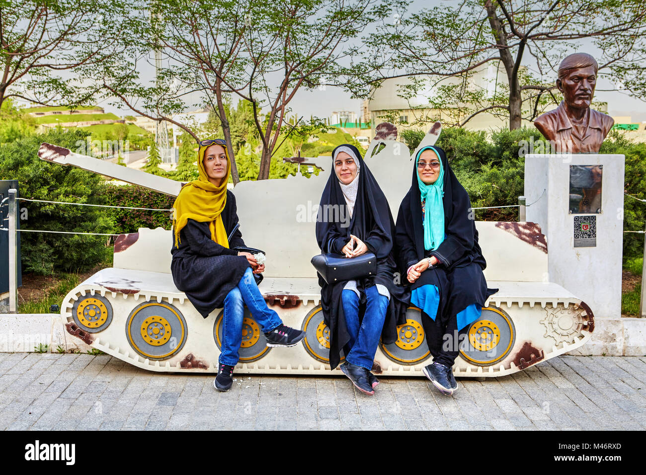 Tehran, Iran - April 28, 2017: Three young Iranian girls in hijabs are sitting on the breadboard model of the tank - Stock Image