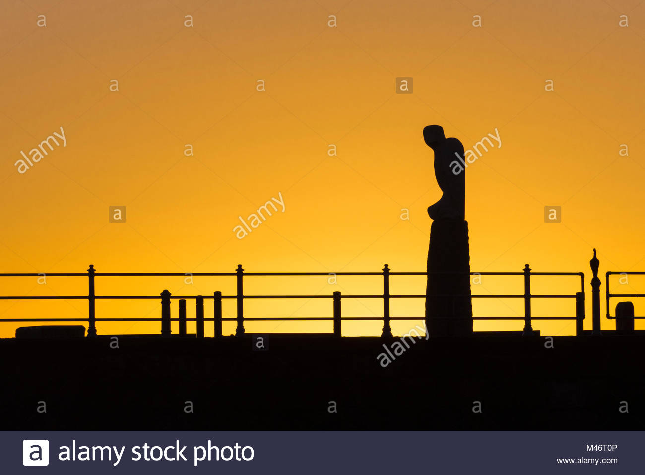 The Mythical Bird sculpture by Gordon Young, part of the Tern Project, is silhouetted against an orange sunset at - Stock Image
