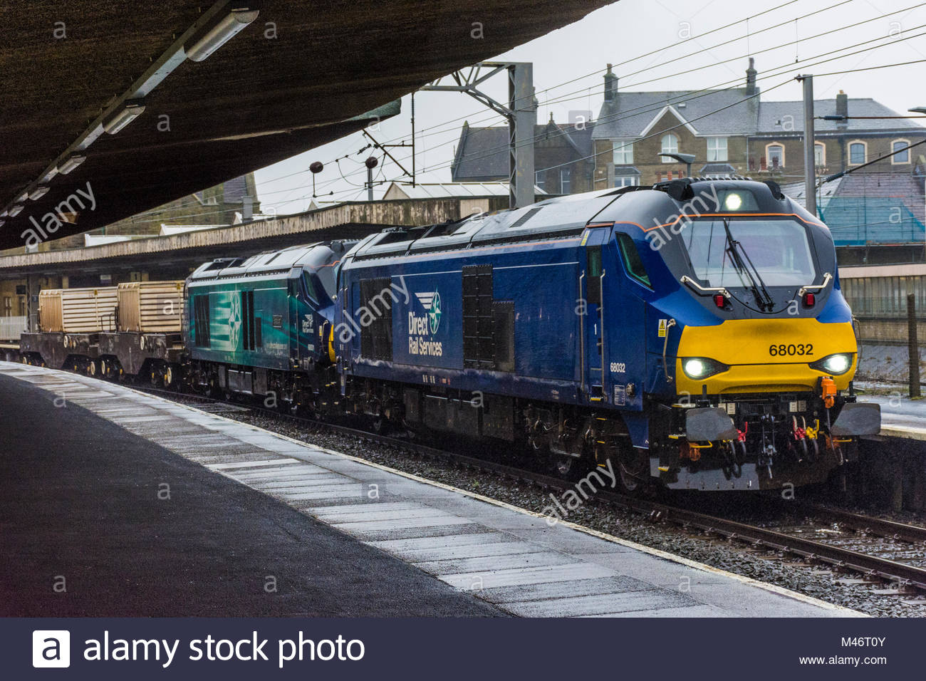 Two diesel locomotives pull goods wagons for carrying nuclear waste through Carnforth Railway Station, Lancashire, - Stock Image
