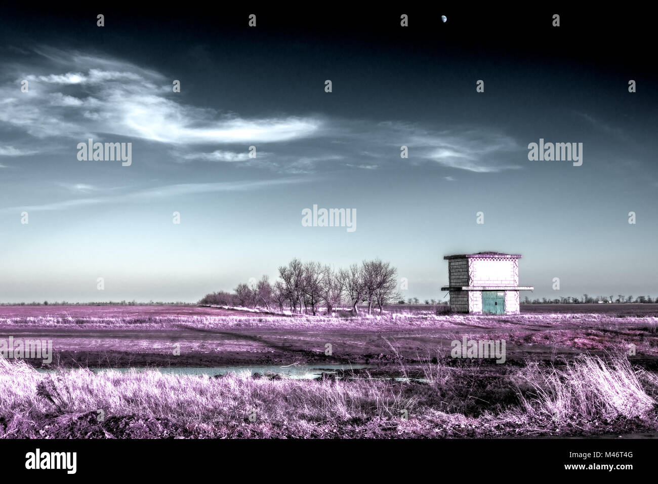 Transforming substation and the moon in the winter sky in infrared colors. Post-apocalyptic infrared landscape. - Stock Image
