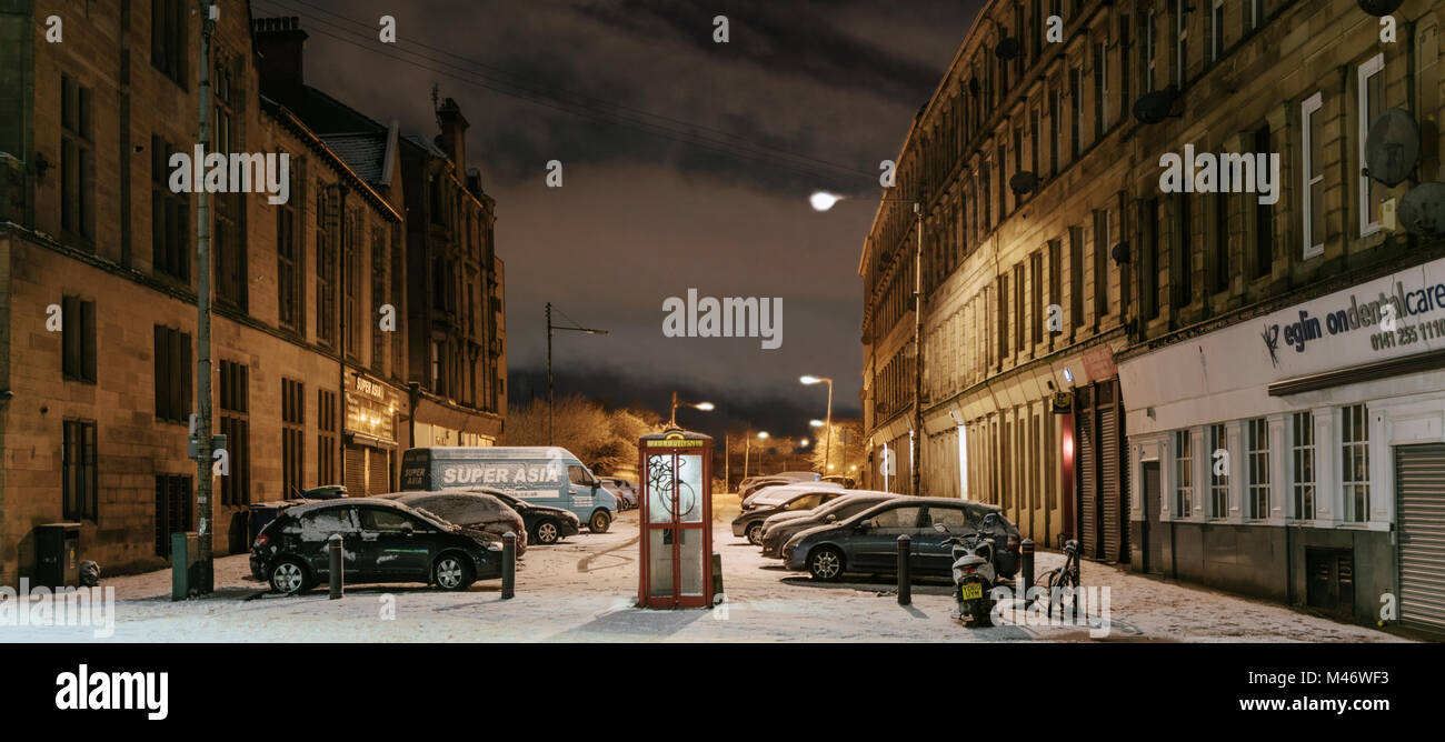 A public phone box in deserted Glasgow city street at night after a fall of snow, Scotland, UK - Stock Image