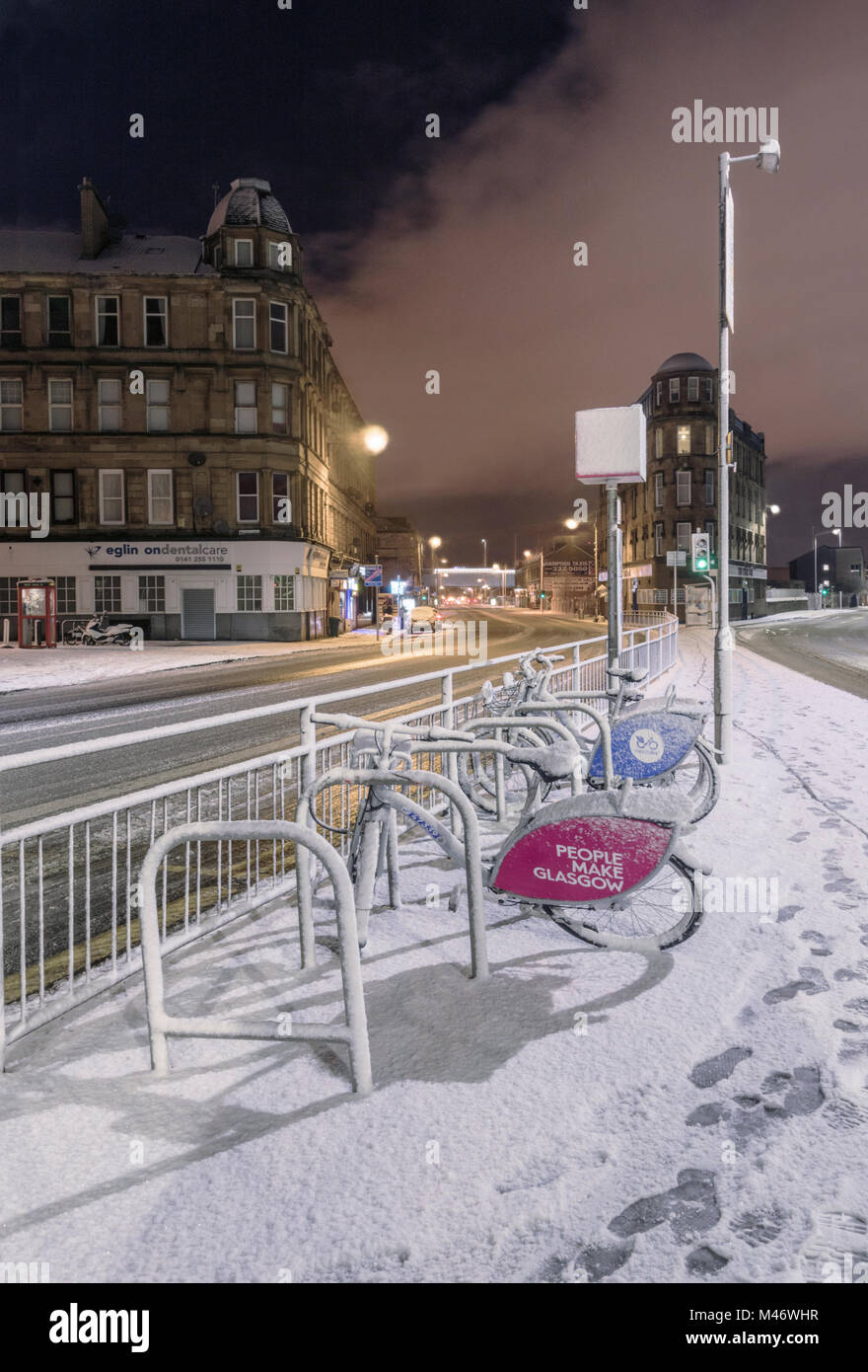 Public bicycle hire station in Glasgow city at night after a fall of snow, Scotland, UK - Stock Image