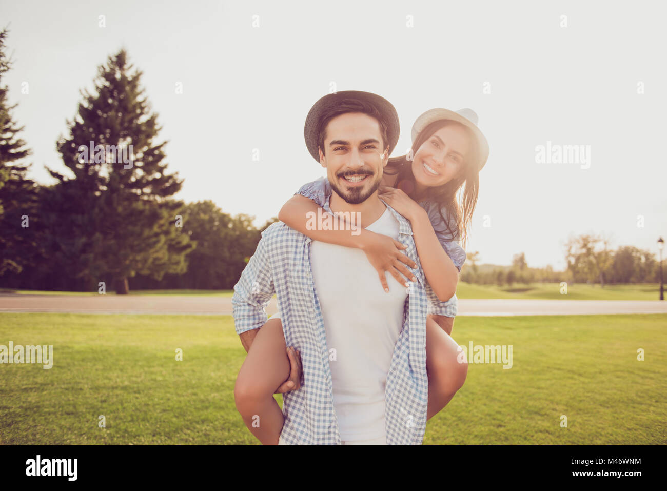 Good day, happiness, friendship concept. Cute sweet partner piggybacking his gorgeous lady, she cuddles to him. - Stock Image