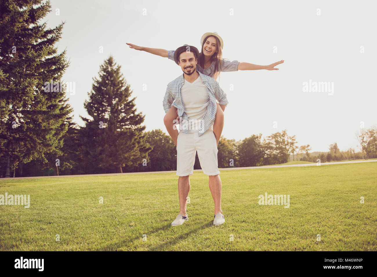 Cute sweet partner piggybacking his lady, she rides him. Date outside, well dressed, excited, lovely. Good day, - Stock Image