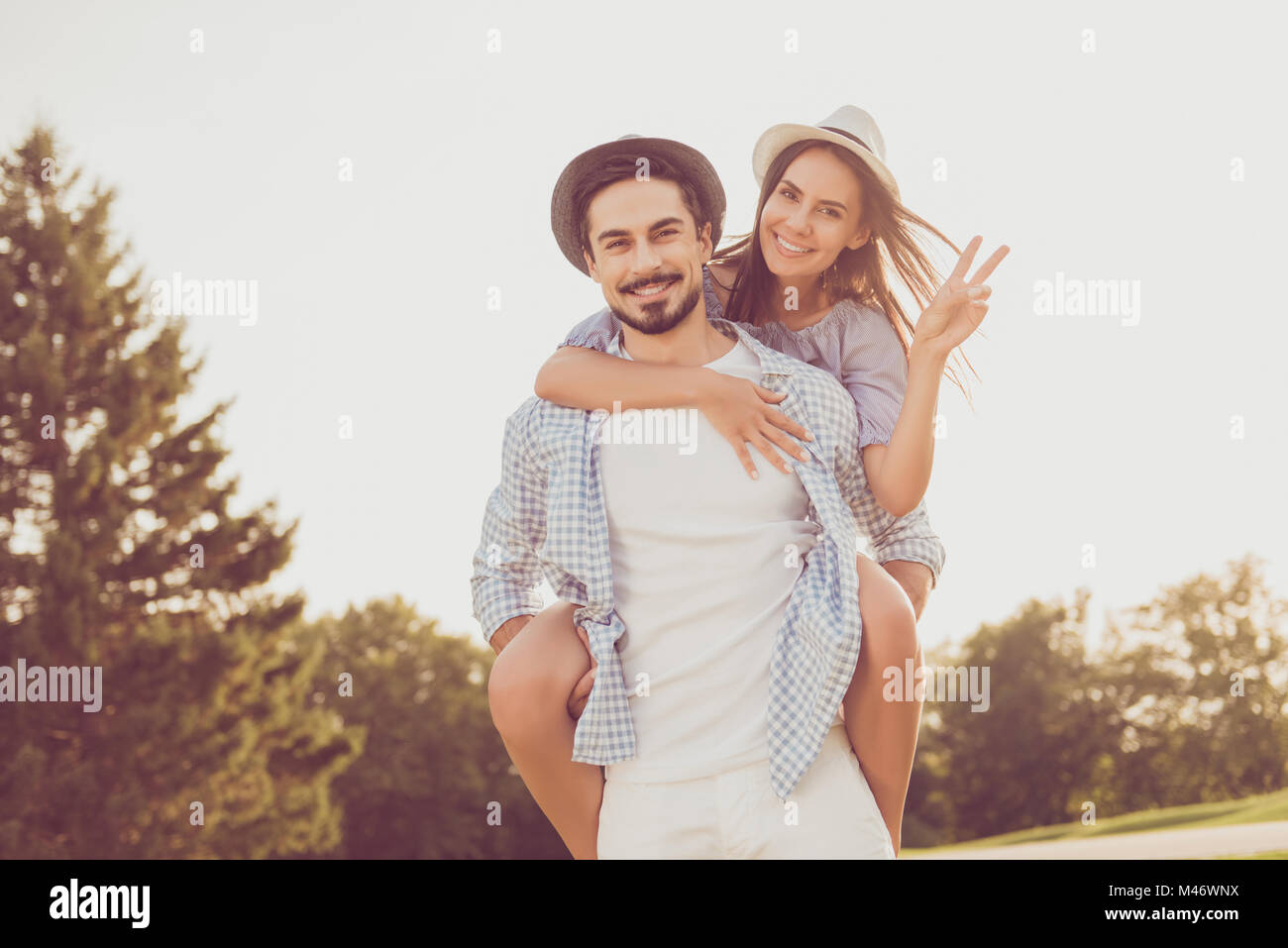 Attractive cute sweet partner piggybacking his gorgeous lady, she cuddles, rides him, shows peace sign. Date outside, - Stock Image