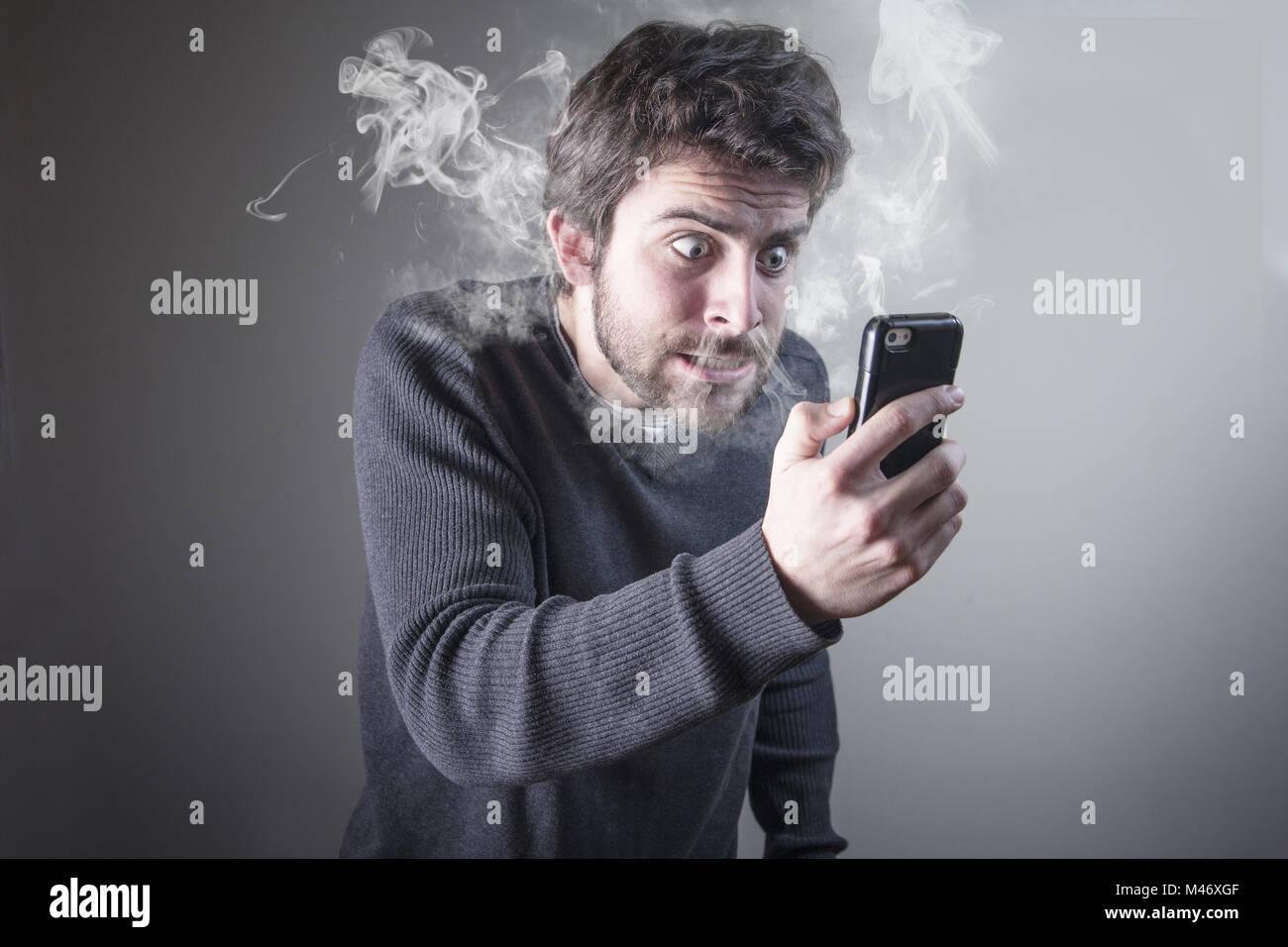 Man furious with his phone smoking with rage - Stock Image