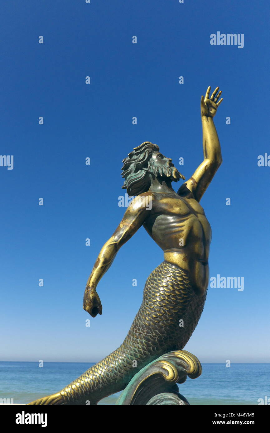 A bronze representation of Triton from classic greek mythology is a fixture on the malecon in Puerto Vallarta, Mexico. - Stock Image