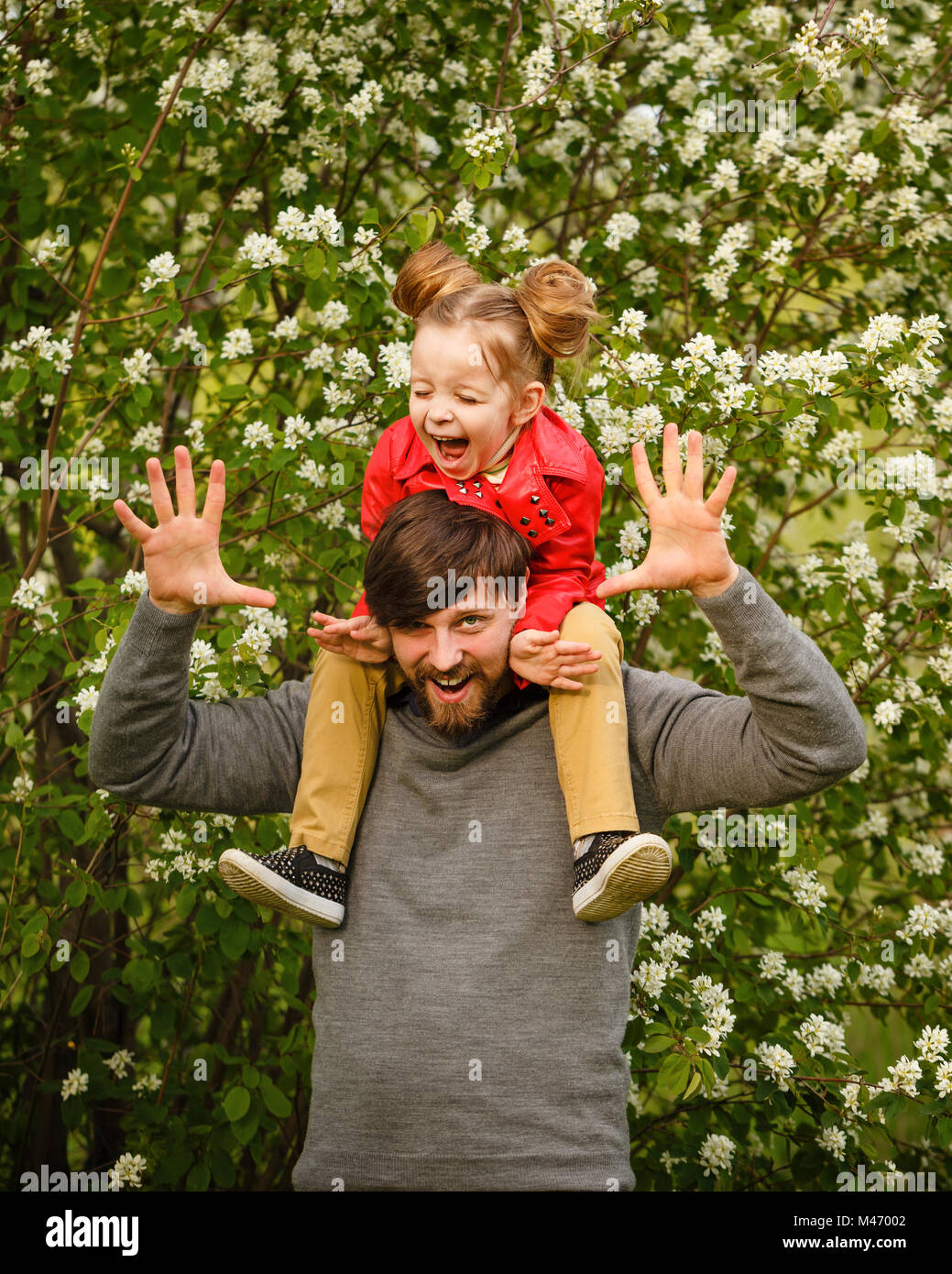 Family time. Father holds on his shoulders a small daughter in a leather jacket. Piggyback. They laugh and fool - Stock Image
