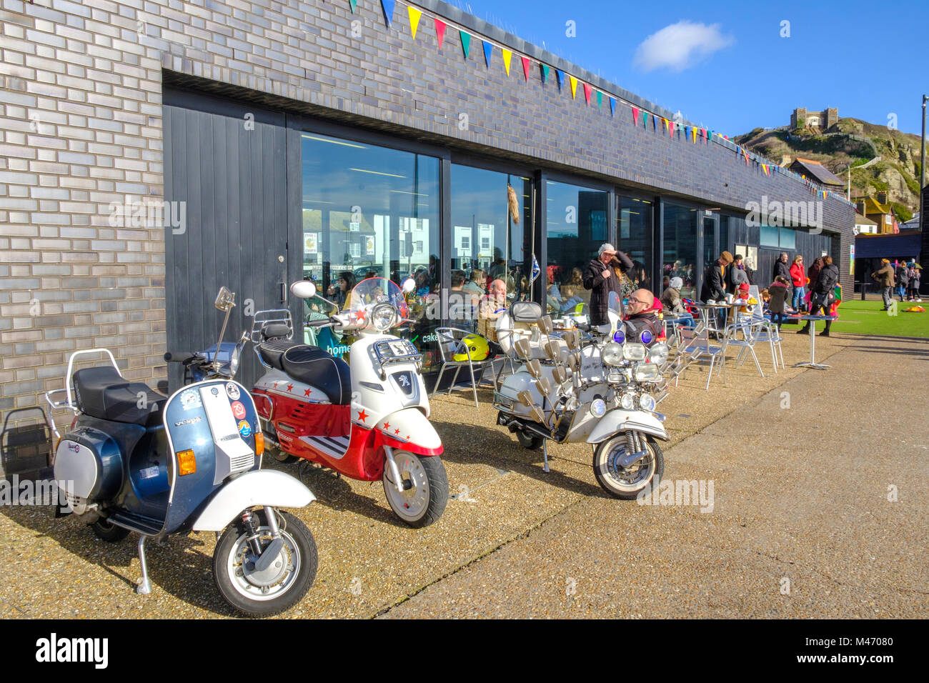 Motor scooters outside eat@ café at Hastings on the seafront Stade, East Sussex, England, UK - Stock Image