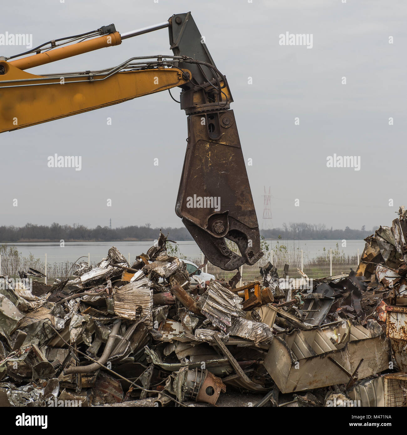 Large tracked excavator working a steel pile at a metal recycle yard, France - Stock Image