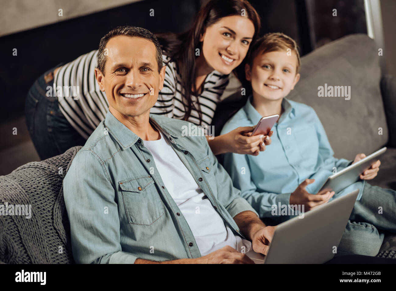 Cheerful family posing while using their gadgets - Stock Image