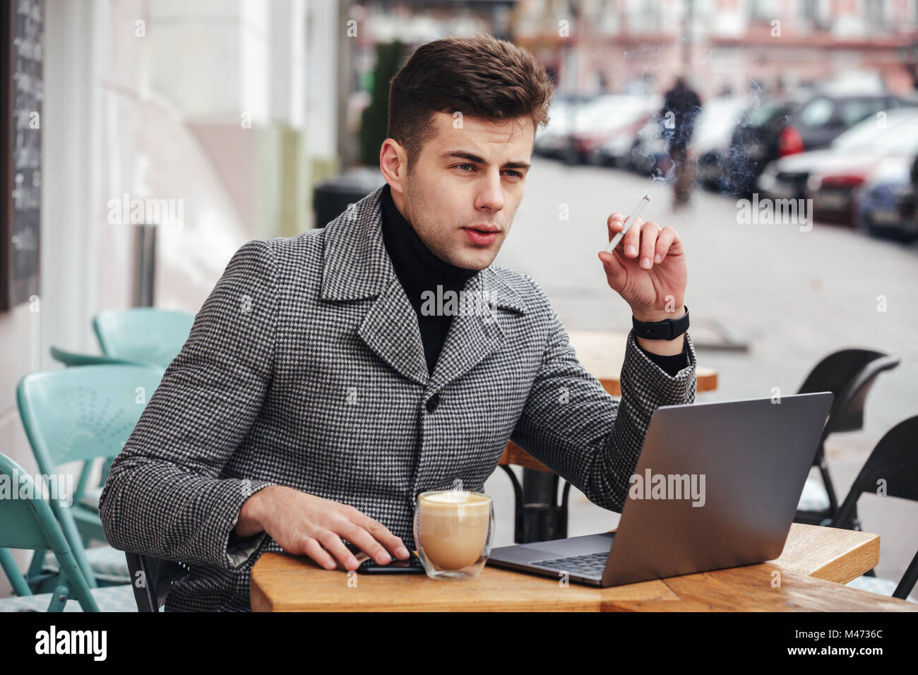 Photo of elegant businessman with brooding look sitting in cafe outside smoking cigarette and drinking cappuccino Stock Photo