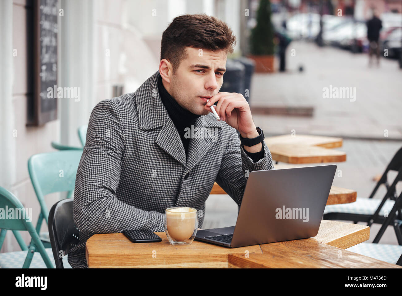Good-looking caucasian guy with brooding look sitting in cafe outside smoking cigarette and drinking cappuccino Stock Photo