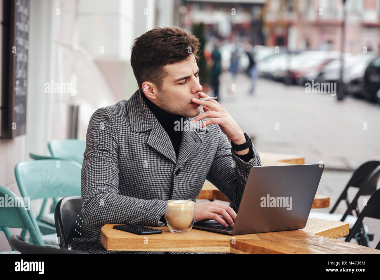 Photo of handsome man in gray coat smoking cigarette and drinking cappuccino while resting in cafe outdoors Stock Photo