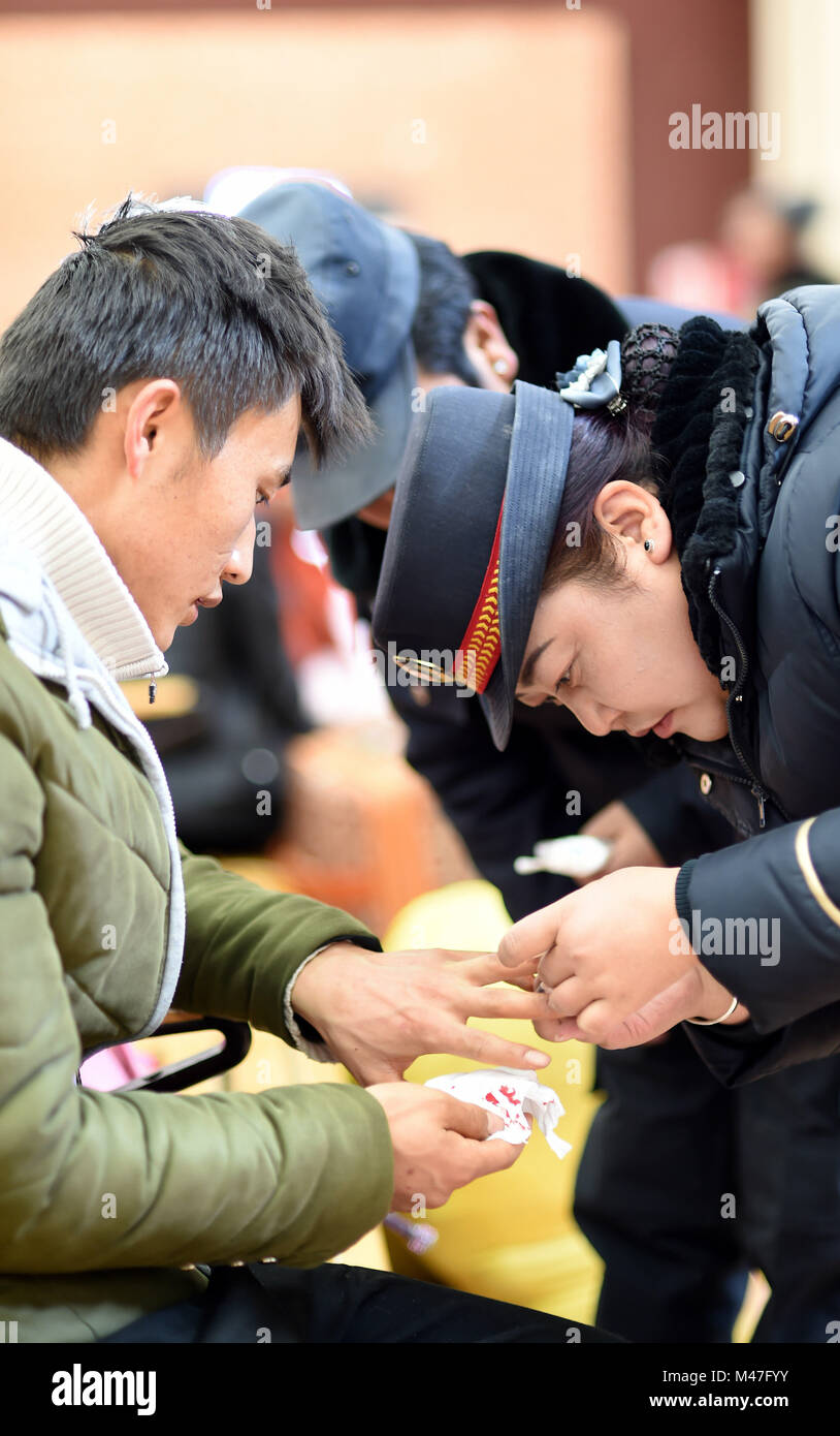 Lhasa, China's Tibet Autonomous Region. 15th Feb, 2018. A staff member helps a passenger bind up a wound at - Stock Image