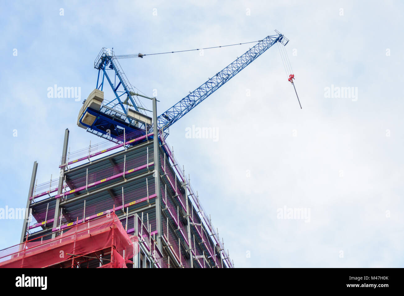 Looking up at a mechanical crane mounted on top of a steel framed building during a construction project in Glasgow, Stock Photo