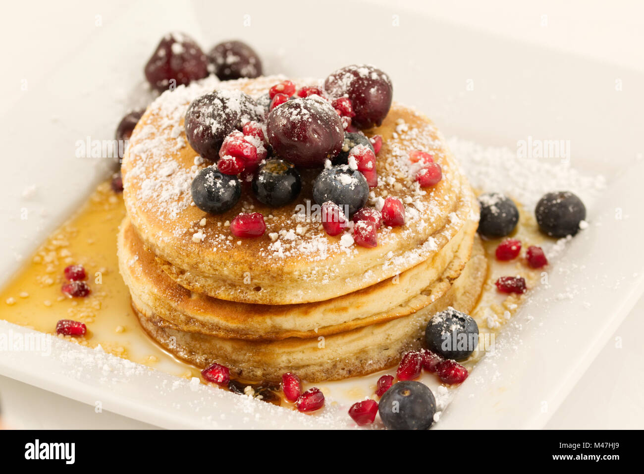 Breakfast pancakes topped with blueberries, pomegranate seeds, cherries and icing sugar (powdered sugar) and maple - Stock Image