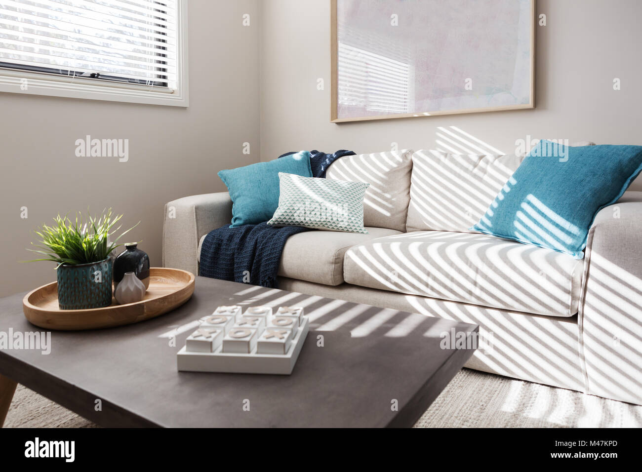 Neutral living room with textured fabrics and teal accents - Stock Image