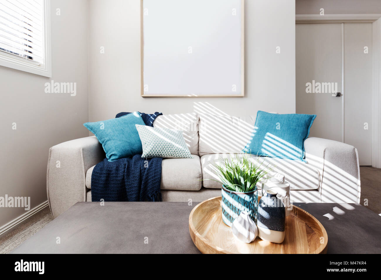 Living room sofa with blank picture mock up for your artwork - Stock Image