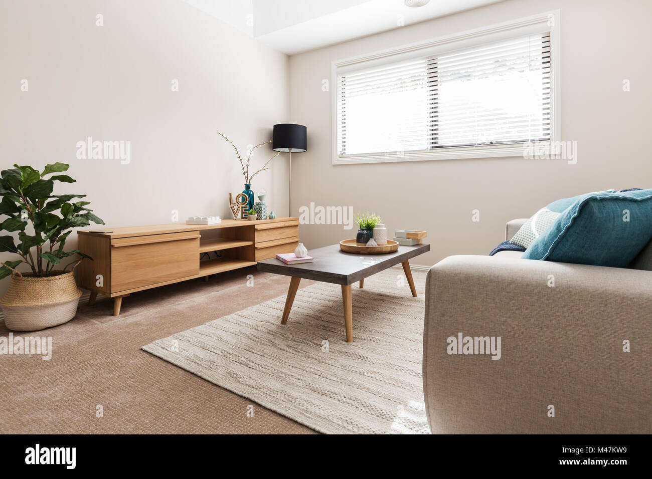 Scandi styled living room with low buffet and indoor plant - Stock Image